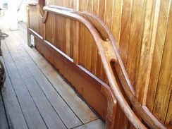 P20089215399	The curved handrail leading towards the stern of the ship.